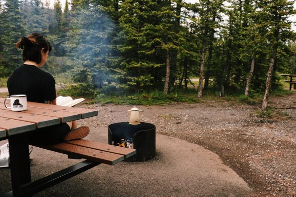 Girl reading on picnic bench. Empty campsite near by. GSI percolator over campfire and Devil's Head mug in foreground.